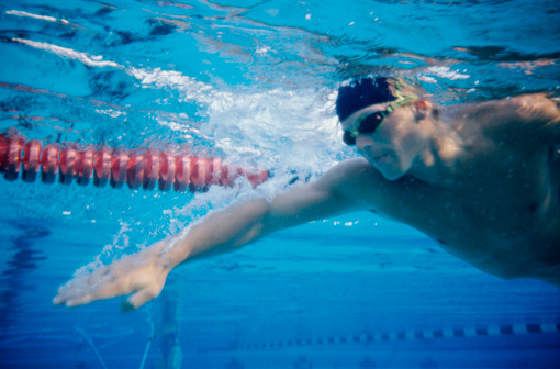 Low angle view of a young man swimming underwater in a swimming pool
